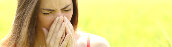 44652575 - woman with allergy coughing in a green color field in summer