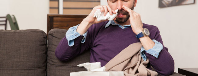 portrait of a sick young man using nasal spray to fight the flu at home