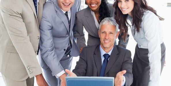 16236267 - young business people standing behind their director proudly showing the laptop